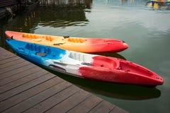 在湖水的两条独木舟小船浮游物  在旁边有木bridg 免版税库存图片