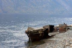 在湖海岸的老捕鱼船 免版税库存照片