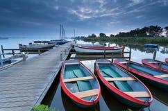 在湖港口的小船黄昏的 免版税库存照片