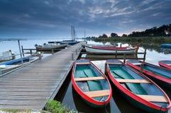 在湖港口的红色小船 库存照片