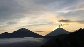 在湖用云彩盖的喷发烟的Batur和阿贡火山上的日出-看见从登上Batur上面在巴厘岛,印度尼西亚 股票视频