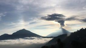 在湖用云彩盖的喷发烟的Batur和阿贡火山上的日出-看见从登上Batur上面在巴厘岛,印度尼西亚 影视素材