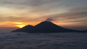 在湖用云彩盖的喷发烟的Batur和阿贡火山上的日出-看见从登上Batur上面在巴厘岛,印度尼西亚 股票录像