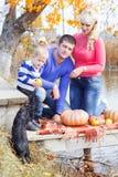 在湖用南瓜,秋天时间附近的年轻家庭 免版税库存照片