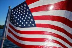 在湖由后照的美国国旗 库存照片