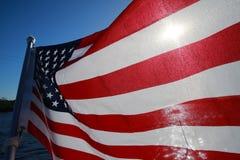 在湖由后照的美国国旗 库存图片