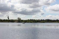 在湖的一个孤立渔船 库存图片