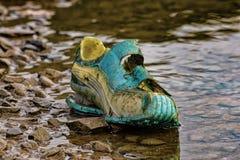在湖的一双老鞋子 免版税图库摄影