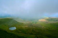 在湖的一幅全景小山的(Llyn Cwm Llwch)在笔y爱好者峰顶,布雷肯比肯斯山,威尔士,英国附近 库存照片
