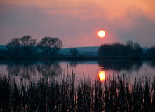 在湖的不可思议的日落在村庄 图库摄影