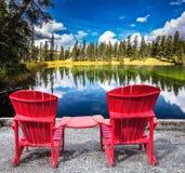 在湖的两把红色塑料椅子 免版税库存图片
