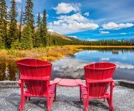 在湖的两把红色椅子 库存照片
