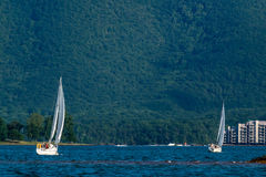 在湖的两艘帆船由山 库存图片