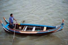 在湖的传统小船在缅甸的U-bein桥梁附近 免版税库存照片