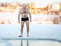 在湖的冬天游泳者冰孔 免版税库存照片