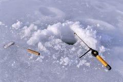 在湖的冰和钓鱼竿的孔在冬天渔 免版税图库摄影