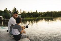 在湖的凉快的爸爸和儿子渔 库存照片