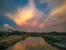 在湖的剧烈的日落在村庄 库存图片