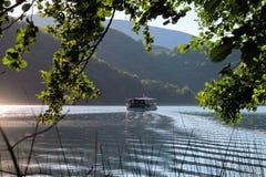 在湖的小船在克罗地亚` s Plitvice Lak的山之间 库存图片