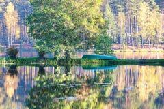 在湖的小船在秋天森林里 图库摄影