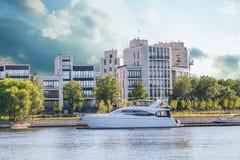 在湖的小船游艇 在背景是公寓、庭院、路和汽车 库存图片