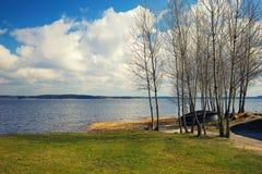 在湖的小船通过树在一个晴朗的春日 免版税库存照片