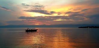 在湖的小船-美好的火热的日落 免版税库存照片