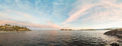 在湖的岩石岸的晴天 免版税图库摄影