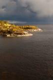在湖的岩石岸的晴天 图库摄影