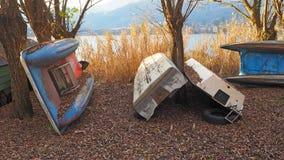 在湖的岸的被放弃的木小船,芦苇的,秋季 免版税图库摄影