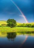 在湖的彩虹,反映在水 免版税库存照片