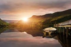 在湖的日出有小船的停泊了在跳船 免版税库存照片