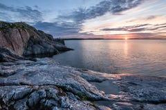 在湖的日出有石海岸的在y的多云早晨天空下 免版税库存图片