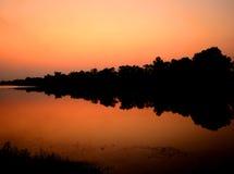 在湖的日落剪影以后 免版税库存图片