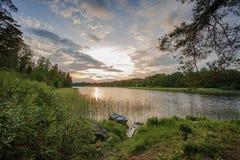 在湖的日落在瑞典 绿色自然颜色和天空蔚蓝与白色云彩 在岸停放的小船 免版税库存图片