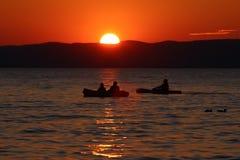 在湖的日落有小船和鸭子的 免版税库存照片