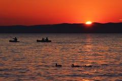 在湖的日落有小船和鸭子的 免版税库存图片