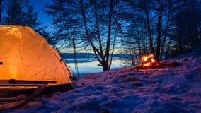 在湖的日落有帐篷和篝火的在冬天 库存图片