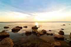 在湖的日落有许多石头的 免版税库存照片