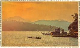 在湖的日落难看的东西减速火箭的样式的 库存照片