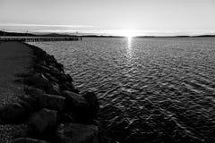 在湖的日落,有太阳的低在天际和岩石在 库存照片