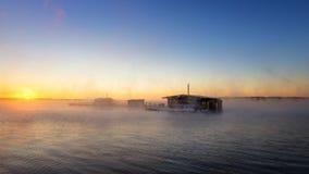 在湖的早晨风景有渔夫雾的` s房子的,俄罗斯,乌拉尔 库存照片