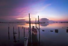 在湖的暮色时间有小船的 库存图片