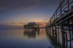 在湖的暮色时间有房子和木头桥梁的 免版税库存照片