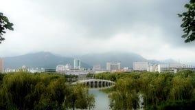 在湖的曲拱桥梁在杨柳公园 城市依靠遥远的小山 影视素材