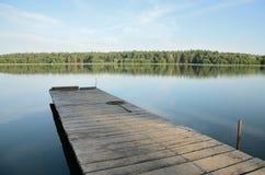 在湖的木码头在无风天气的下午的 免版税库存照片