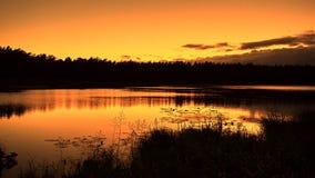 在湖的橙色日落 免版税库存图片