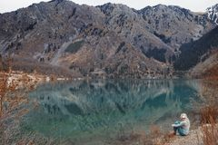 在湖的水的边缘的妇女听的音乐 免版税库存照片