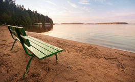 在湖的海岸的绿色长木凳 免版税库存照片