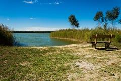 在湖的海湾的附近长凳 免版税图库摄影